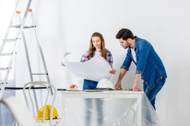 couple looking at blueprint during home repairs