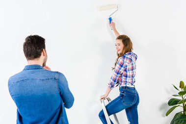 smiling girlfriend painting wall and looking at boyfriend