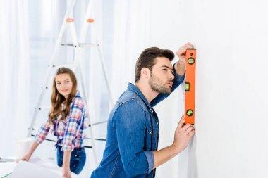 handsome man measuring wall flatness
