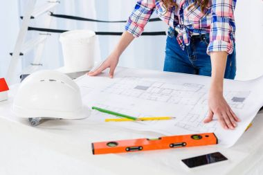 cropped image of architect holding blueprint on table