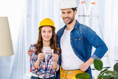 smiling couple in helmets holding home repair card