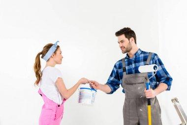 side view of boyfriend giving girlfriend bucket of paint