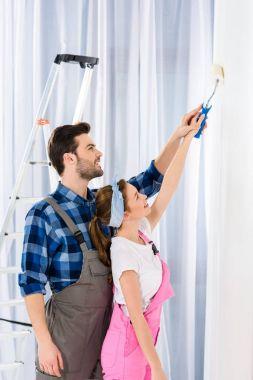 boyfriend helping girlfriend painting wall