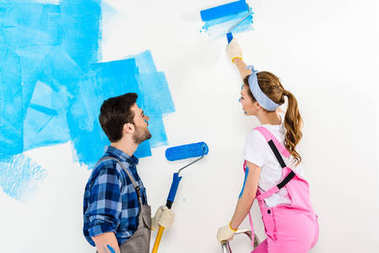 boyfriend and girlfriend painting wall with blue paint