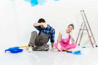 tired boyfriend and girlfriend sitting on floor during repairs