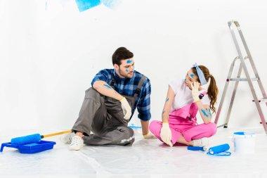 boyfriend and girlfriend sitting on floor in room with repairs
