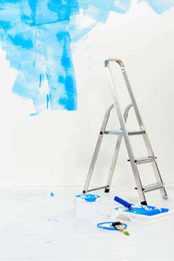 ladder and paint roller brush in blue paint