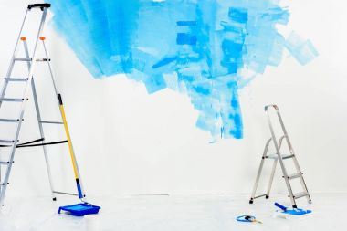Ladders and paint roller brushes in blue paint stock vector