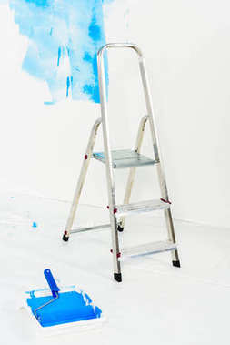 Ladder and paint roller brush in blue paint stock vector