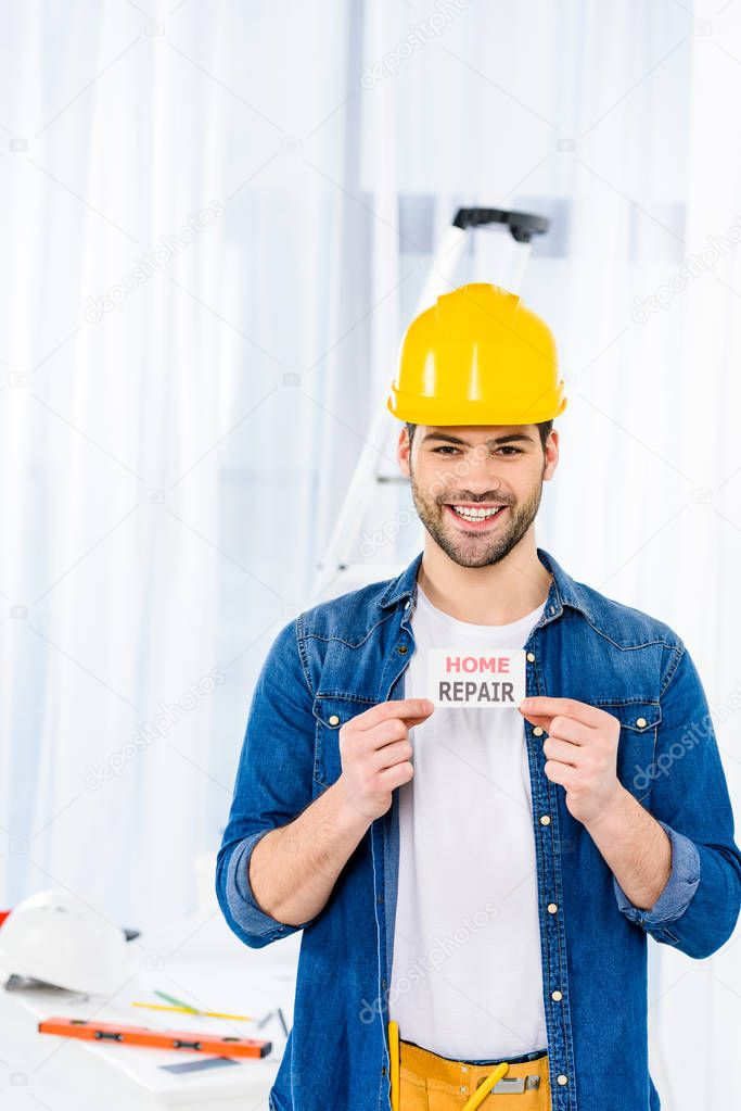 smiling handsome man holding home repair card