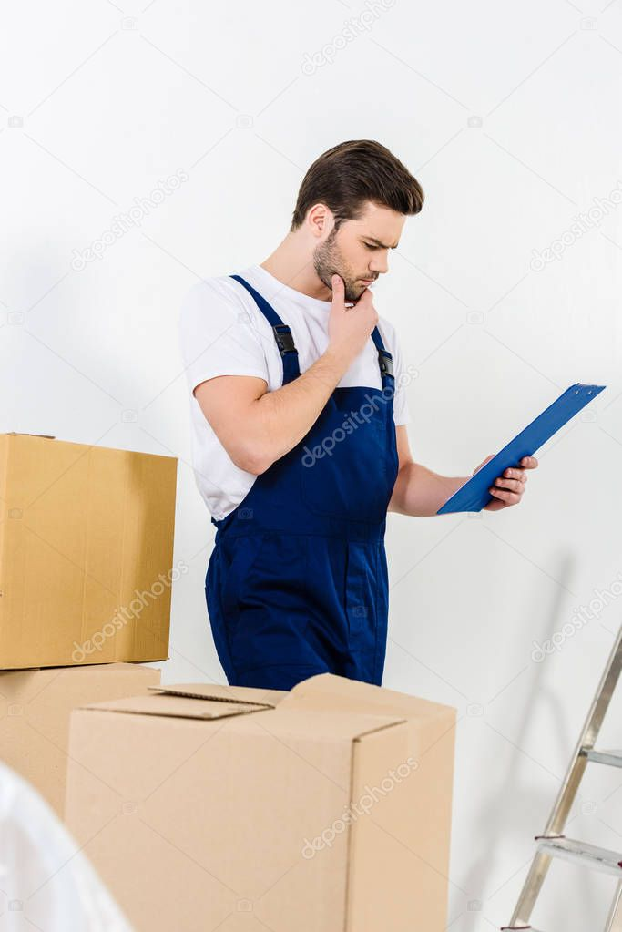 thoughtful relocation service worker looking at clipboard