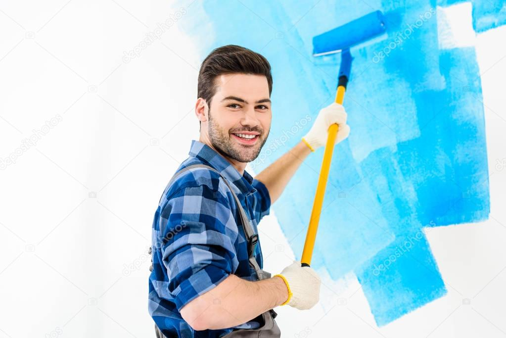 smiling handsome man painting wall with blue paint