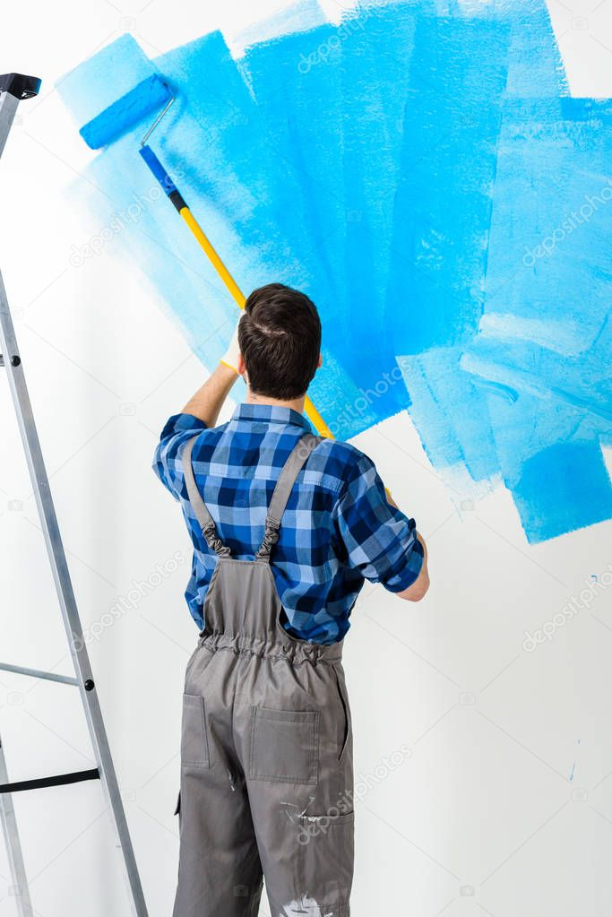 rear view of man painting wall with blue paint