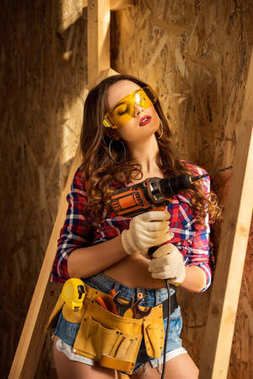 beautiful sexy woman with tool belt and electric drill posing on construction