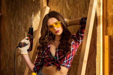 sexy woman in goggles with electric drill posing on construction