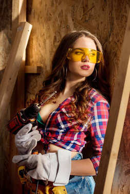 beautiful sexy woman in goggles with electric drill posing on construction