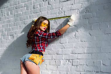 sexy woman in goggles with tool belt measuring white brick wall