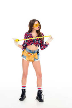 attractive sexy girl posing with tool belt and tape meaure, isolated on white