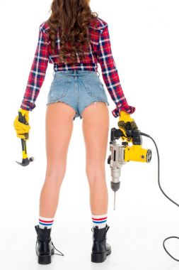 cropped view of sexy girl in gloves holding hammer and electric drill, isolated on white