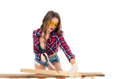 sexy girl in goggles working with saw, isolated on white