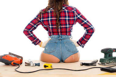 back view of sexy girl sitting on wooden table with tools, isolated on white