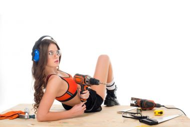 sexy woman in protective headphones posing with electric drill at wooden table with tools, isolated on white