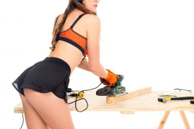 cropped view of girl in hardhat working with grind tool at wooden table with tools, isolated on white