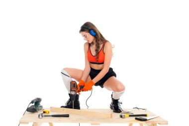 beautiful girl in protective headphones working with electric drill at wooden table with tools, isolated on white