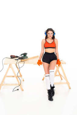 sexy girl in protective headphones sitting on wooden table with equipment, isolated on white
