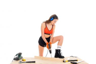 attractive girl in protective headphones working with electric drill at wooden table with tools, isolated on white