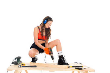 sexy girl in protective headphones working with electric drill at wooden table with tools, isolated on white