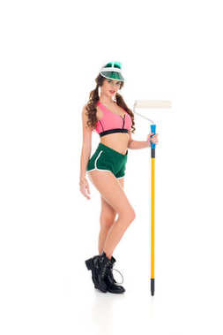 attractive woman in visor holding painting roller, isolated on white