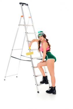 beautiful girl in visor holding painting roller near ladder, isolated on white