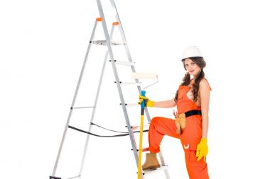 beautiful workwoman in uniform holding painting roller near ladder, isolated on white