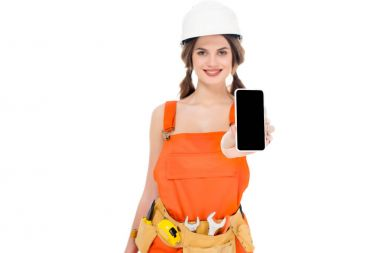smiling workwoman in uniform holding smartphone with blank screen, isolated on white