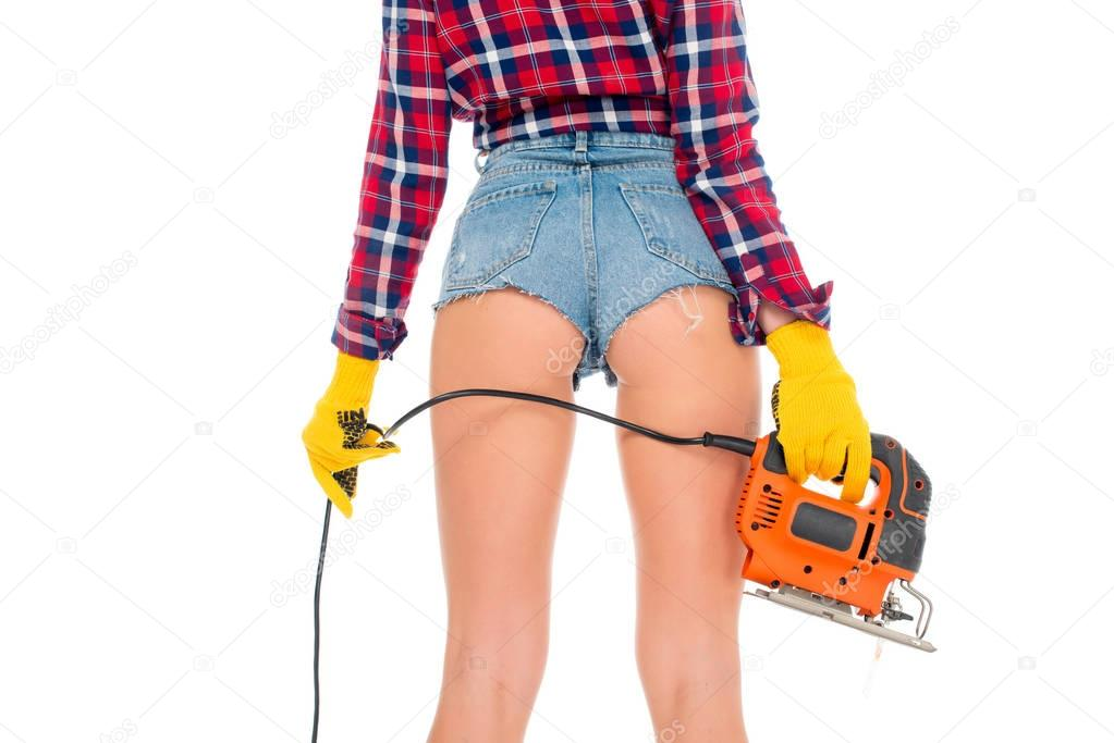back cropped view of sexy girl with electric fret saw, isolated on white