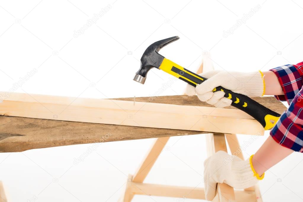 cropped view of girl working with hammer and nail, isolated on white