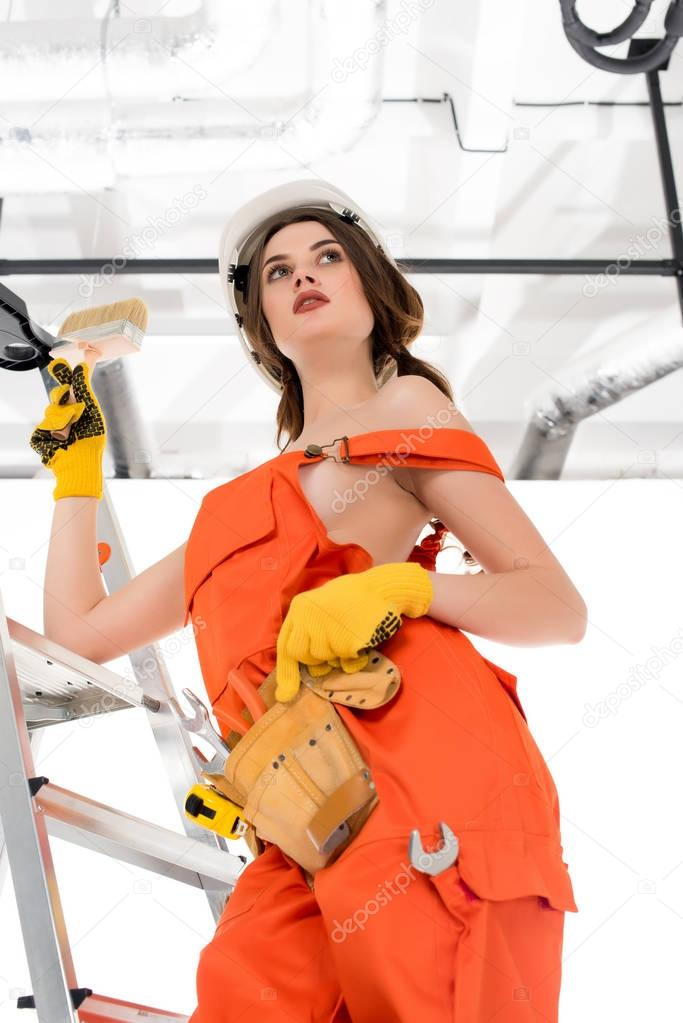 attractive workwoman in uniform with tool belt holding brush and standing on ladder