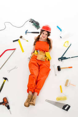 overhead view of girl in overalls and hardhat lying on floor with different equipment and tools, isolated on white