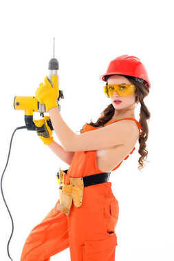 workwoman in overalls and hardhat holding electric drills, isolated on white