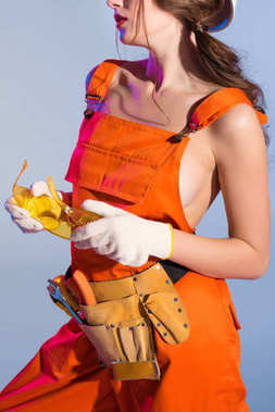 cropped view of girl in overalls with tool belt and goggles, isolated on blue