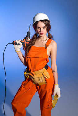 beautiful girl in overalls and safety helmet with tool belt holding electric drill, on blue
