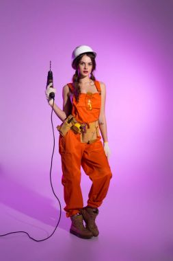 sexy workwoman in overalls and safety helmet with tool belt holding electric drill, on purple