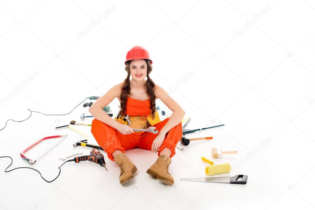 girl in overalls sitting on floor with different equipment and tools, isolated on white