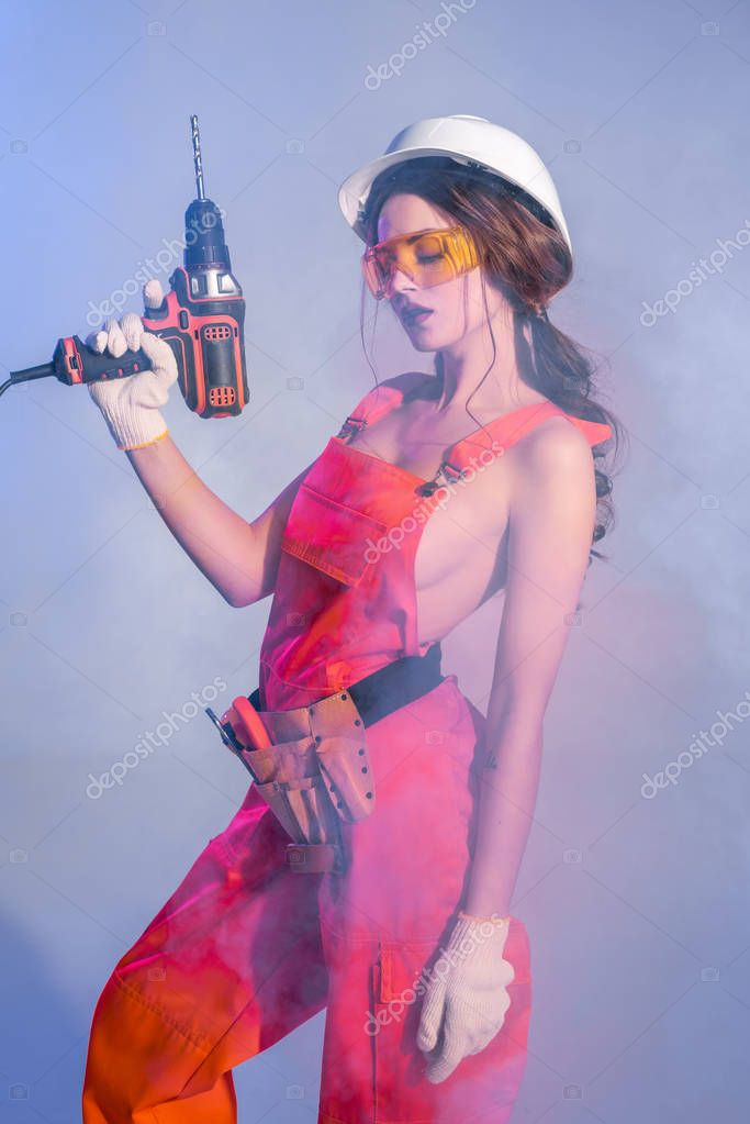 beautiful girl in overalls with tool belt, goggles and electric drill, on blue with smoke