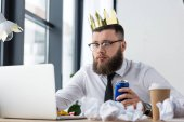 Fotografie portrait of businessman with paper crown on head and soda drink in hand working on laptop at workplace in office