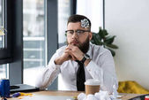 Photo portrait of pensive businessman with bow on head at workplace in office