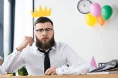 Fotografie portrait of businessman with paper crown at workplace in office