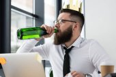 Fotografie businessman with paper crown on head drinking champagne at workplace in office
