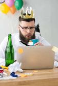 portrait of businessman with paper crown on head looking at laptop screen at workplace in office